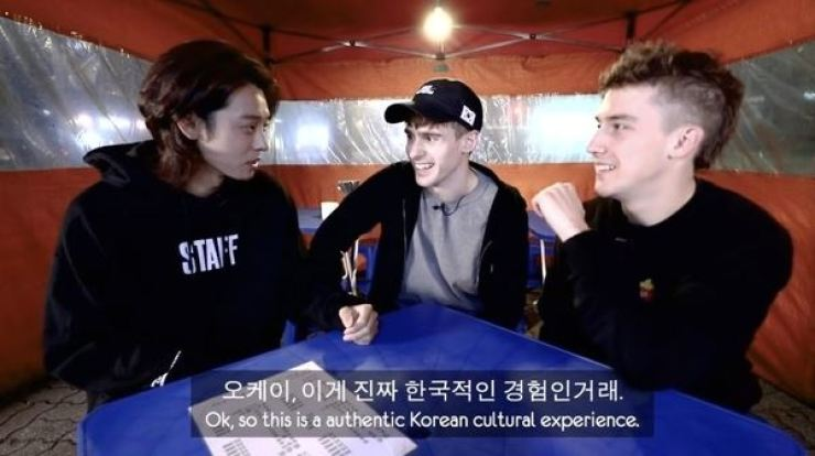 In a scene from British YouTuber Josh Carrott's clip posted on December 2018, singer-songwriter Jung Joon-young, left, introduces the Korean drinking culture to Carrott, center, and guest Ollie Kendal in a Korean street eatery-tent 'pojangmacha.' Carrott deleted the video shortly after allegations of Jung's sex video filming and distribution were reported on Mar. 11. Screen capture from YouTube