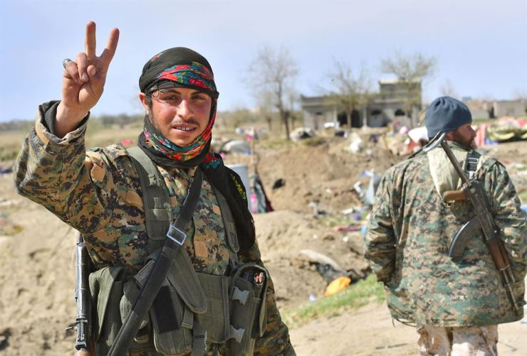 A picture taken on March 23 shows a fighter of the U.S.-backed Kurdish-led Syrian Democratic Forces flashing the V for victory sign in the fallen Islamic State group's last bastion in the eastern Syrian village of Baghuz after defeating the jihadist group. Kurdish-led forces pronounced the death of the Islamic State group's nearly five-year-old 'caliphate' on March 23 after flushing out diehard jihadists from their very last bastion in eastern Syria. AFP