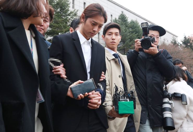 Police escort singer Jung Joon-young out of the Seoul Central District Court, southern Seoul, Thursday, after a court review on whether to issue an arrest warrant for him. The warrant was issued later in the day on charges that Jung illegally shared sexually explicit videos of women taken without their consent online. / Yonhap