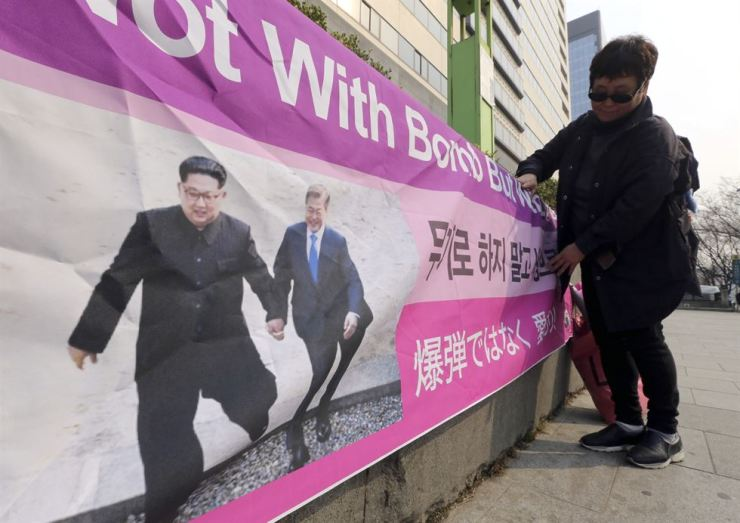 A woman displays a banner with a photo of North Korean leader Kim Jong-un and South Korean President Moon Jae-in, right, promoting peace on the Korean Peninsula, in Seoul, March 19. AP-Yonhap