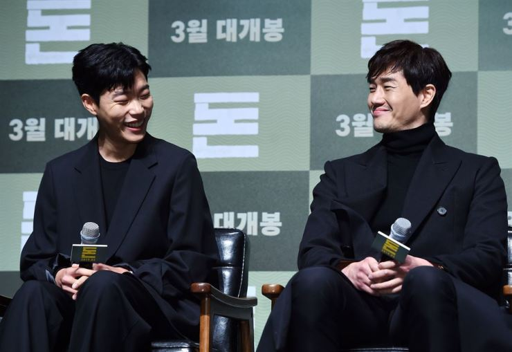 Actors Ryu Jun-yeol, left, and Yoo Ji-tae laugh at a news conference for crime film 'Money' at a CGV movie theater in southern Seoul on Feb. 11. In the box office hit, Yoo, who plays a client, offers a secret offer to stockbroker Ryu.