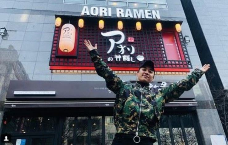 Seungri poses before an Aori Ramen restaurant. Captured from Seungri's Instagram