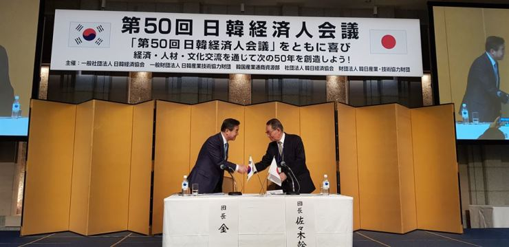 Korea-Japan Economic Association Chairman Kim Yoon, left, shakes hands with Japan-Korea Economic Association Chairman Mikio Sasaki after adopting a joint statement during the 50th meeting between the two groups in Tokyo in this file photo from May 16, 2018. Courtesy of Korea Japan Economic Association
