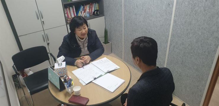 A worker at Seocho-gu Office in southern Seoul explains various services available at the support center for single-person households in the district. / Courtesy of Seocho-gu Office