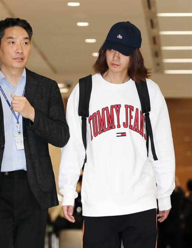 Jung Joon-young, right, arrives at Incheon International Airport, Tuesday, amid allegations that he secretly filmed women he was having sex with and shared the videos with acquaintances. / Korea Times photo by Hong In-ki