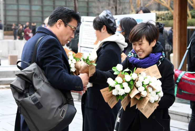A member of Korea Women's Hotline hands out white roses in Gwanghwamun Plaza to celebrate International Women's Day last March 8. This year they will hand out yellow roses. / Korea Times file