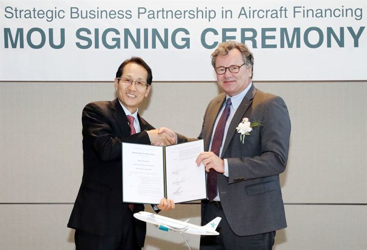 KEB Hana Bank CEO Ji Sung-kyoo, left, shakes hands with Arena Aviation CEO Patrick Den Elzen at the bank's head office in Seoul, Friday. Courtesy of KEB Hana Bank
