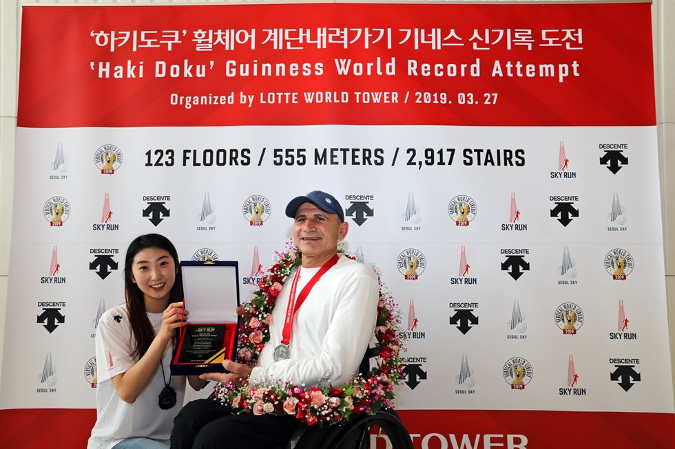 Albanian para-cyclist Haki Doku climbs down the stairs of Lotte World Tower in Seoul, setting Guinness record in 'Most stairs descended in a wheelchair,' Wednesday. He descended the 2,917 stairs of the nation's tallest building in 49 minutes and 56 seconds, breaking the previous record he set in 2018. Courtesy of Lotte World Tower