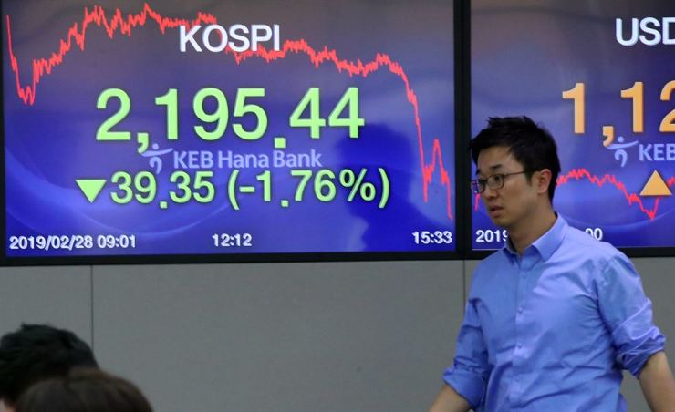 A dealer passes by an electronic sign at KEB Hana Bank headquarters in Seoul, Thursday. The KOSPI closed down at 2,195.44 points on news of the collapse of the U.S.-North Korea summit. Yonhap