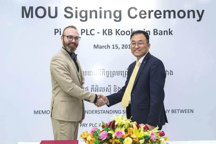 Choi Chang-su, right, managing director of KB Kookmin Bank's global business, shakes hands with Pi Pay CEO Tomas Pokorny after forging ties in digital banking at KB's office in Phnom Penh, March 15. Courtesy of KB Kookmin Bank