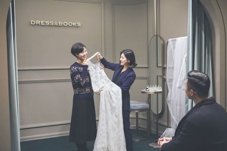 A woman tries on a wedding dress at wedding book's store in Cheongdam-dong, Seoul, Thursday. / Courtesy of wedding book