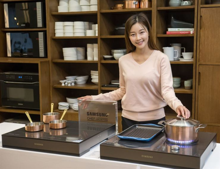 A model poses with Samsung Electronics' induction ranges at the Sempio Korean Taste Space in Seoul, Tuesday. / Courtesy of Samsung Electronics