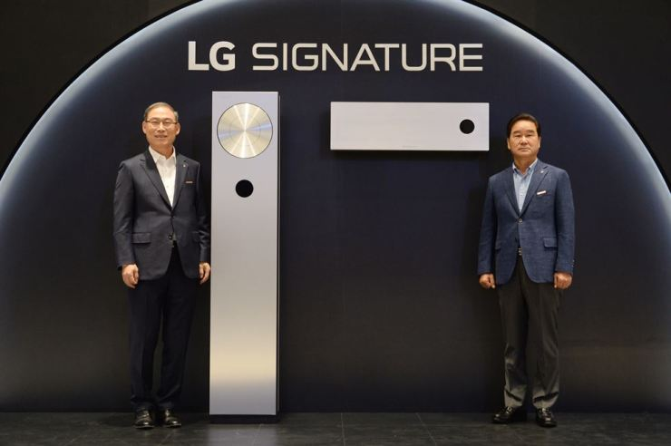 Song Dae-hyun, left, president of home appliance and air solution division at LG Electronics, and Choi Sang-gyu, president of LG's Korean sales and marketing operations pose with the firm's new air conditioners during a press conference at LG Science Park in southwestern Seoul, Tuesday. / Courtesy of LG Electronics