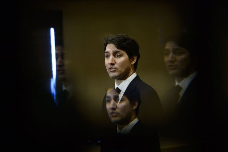 Canada's Prime Minister Justin Trudeau is seen through a bevelled pane of glass in a door as he takes part in a news conference in Iqaluit, Nunavut, Canada, March 8. AP