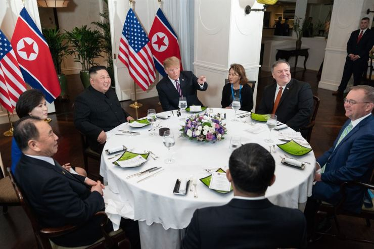 U.S. President Donald Trump and North Korean leader Kim Jong-un speak during a dinner at the Sofitel Legend Metropole Hanoi Hotel in the Vietnamese capital, Wednesday. / Yonhap