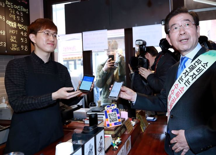 Seoul Mayor Park Won-soon purchases coffee using Zero Pay QR code money transfer at a cafe in Hongdae Gyeongui Line Forest Park, Yeonnam-dong, Seoul, during a Zero Pay promotion tour of the area, Monday. / Yonhap