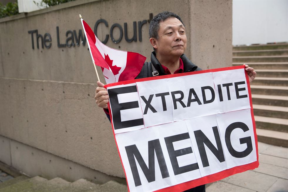 Kuang Yang burns a Chinese flag to protest human rights abuses, outside British Columbia Supreme Court, in Vancouver on March 6, 2019, as Huawei Chief Financial Officer Meng Wanzhou appears in court appearance. AFP-Yonhap
