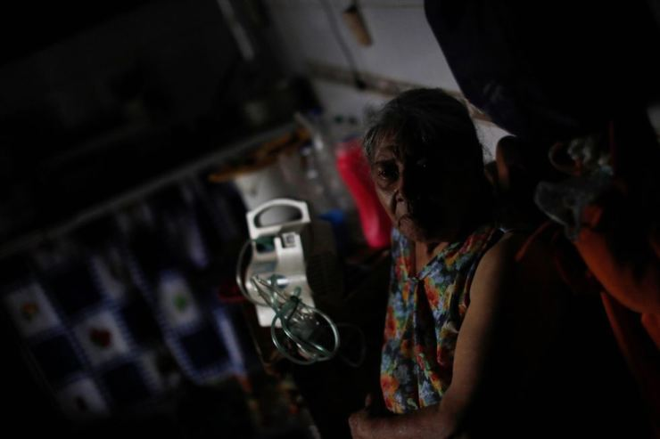 Celedonia Angulo sits next to her nebuliser in her house during a blackout in Catia slum in Caracas, Venezuela March 8, 2019. Reuters-Yonhap