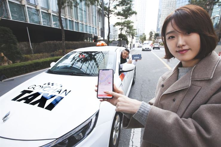 A deaf driver who uses SK Telecom's T Map Taxi app and a model promote the telecom firm's taxi-hailing app designed exclusively for hearing-impaired drivers. / Courtesy of SK Telecom