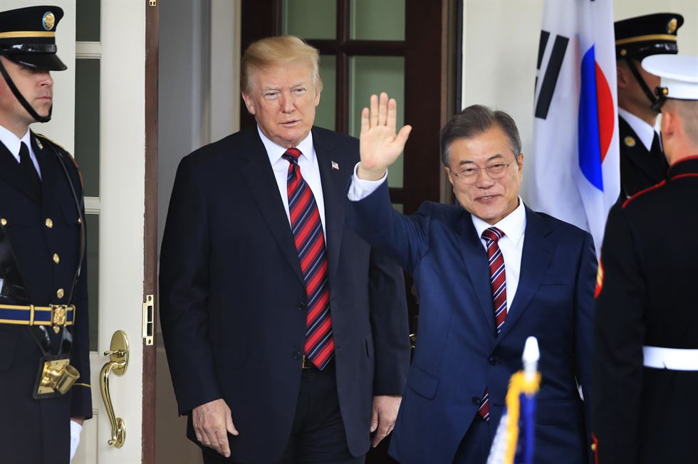 U.S. President Donald Trump and President Moon Jae-in shake hands after signing a trade agreement last September. AP-Yonhap