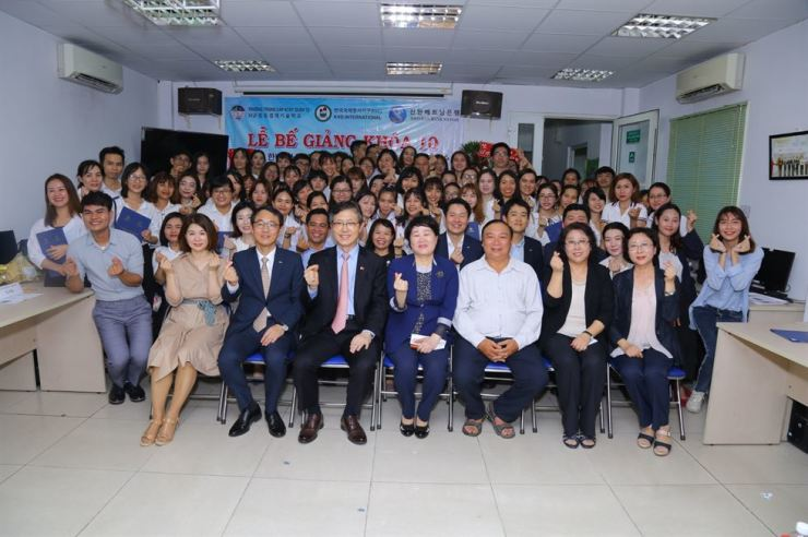 Shinhan Bank Vietnam CEO Shin Dong-min, front row second from left, poses with Vietnamese students who completed the bank's 10th job training program, Wednesday, at the bank's office in Ho Chi Minh City. The bank has been providing education in Korean language, computer programming and financial accounting over the past six years. Courtesy of Shinhan Bank