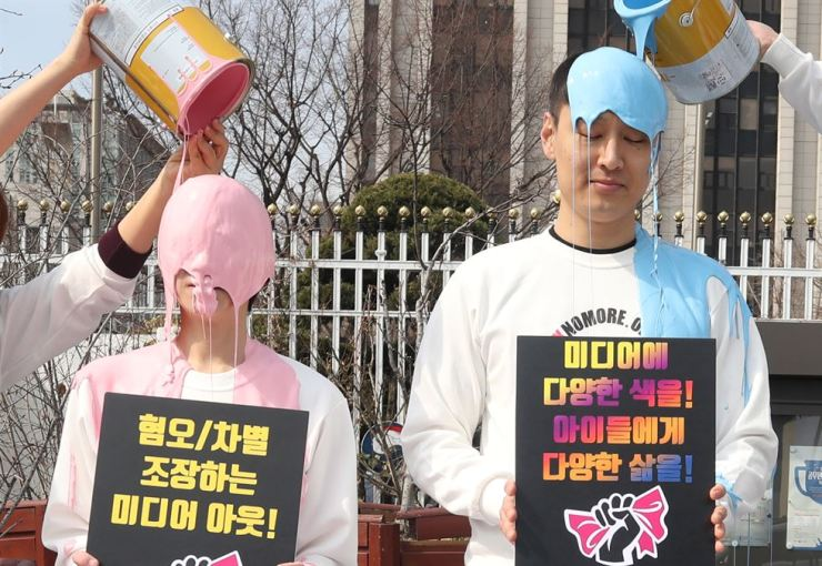 Members of Political Mamas, a civic group, get covered in paint during the 'Pink No More' campaign in front of the Government Complex Seoul, Thursday. During the campaign, the group will collect examples of gender-stereotyped media programs and recommend the producers correct the practice. /Yonhap