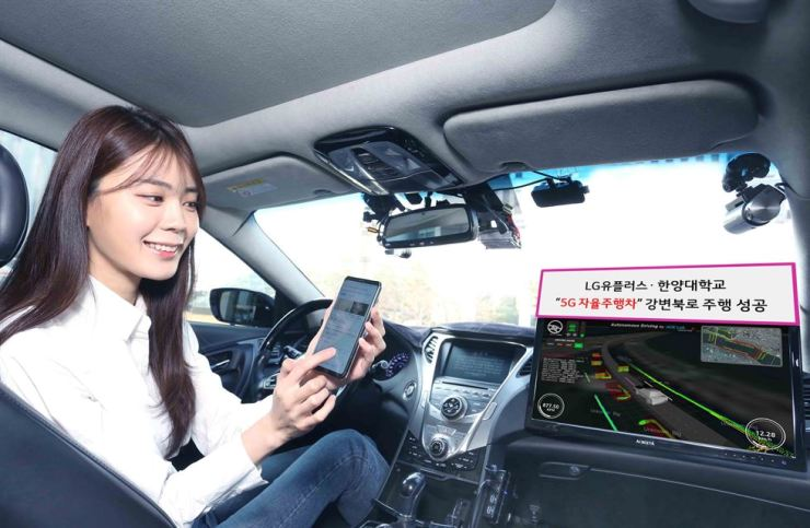 A model uses her mobile phone while riding in an A1, a 5G self-driving car, during a demonstration jointly conducted by LG Uplus and Hanyang University in the busy streets of Seoul, Monday. / Courtesy of LG Uplus
