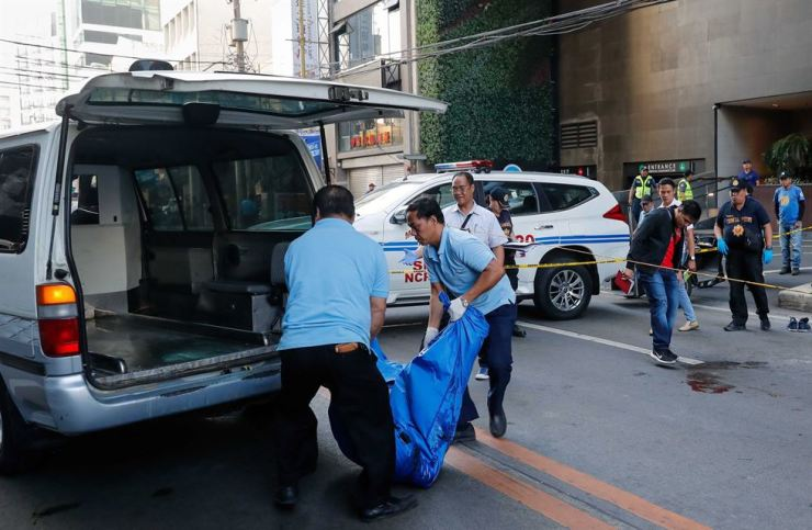 The bodies of two Koreans are loaded into a van in front of a hotel in Makati, Philippines, on March 22. Police are still investigating. EPA
