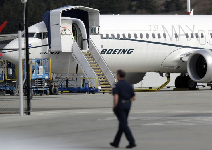 In this March 14 file photo, a worker walks next to a Boeing 737 MAX 8 airplane parked at Boeing Field in Seattle. U.S. prosecutors are looking into the development of Boeing's 737 Max jets, the same day French aviation investigators concluded there were 'clear similarities' in the crash of an Ethiopian Airlines Max 8 last week and a Lion Air jet in October. AP