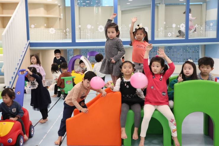 Children of POSCO Daewoo employees pose for a photo during the opening ceremony of a second daycare center at the trading company's headquarters in Incheon, Thursday. Occupying an 820-square-meter space at the headquarters, the new center can provide care for 100 children. Alongside the first center, the two can accommodate all of its employees' daycare needs. Courtesy of POSCO Daewoo