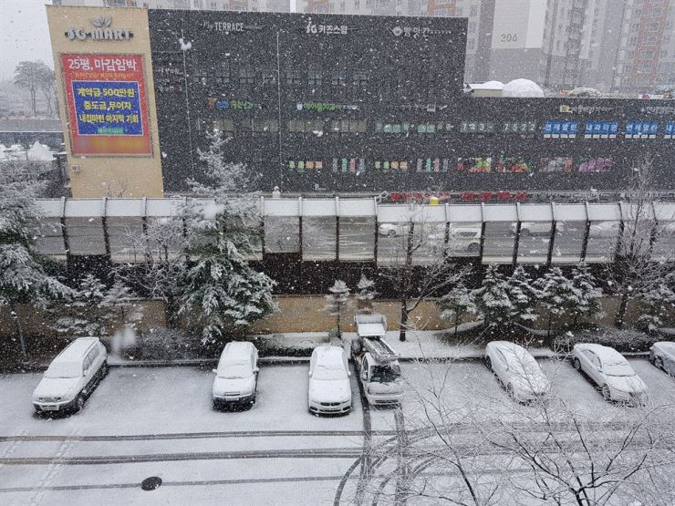 Parked cars are covered with a coating of snow in Wonju, Gangwon Province, Saturday. Up to 5 centimeters of snow fell in some parts of the province as an unseasonal cold spell has gripped the country. Southern regions had showers and strong winds. Sunday morning is forecast to be clear but temperatures are forecast to fall to near zero, the Korean Meteorological Administration said. / Yonhap