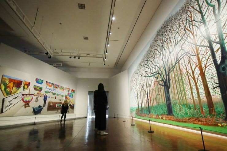 Visitors have a look at British artist David Hockney's 'Bigger Trees Near Warter' or 'Ou Peinture Sur Le Motif Pour Le Nouvel Age Post' (2007), right, and 'In the Studio, December 2017' (2017) currently on display at 'David Hockney,' the artist's first-ever solo exhibition in Asia, at the Seoul Museum of Art, Thursday. Yonhap
