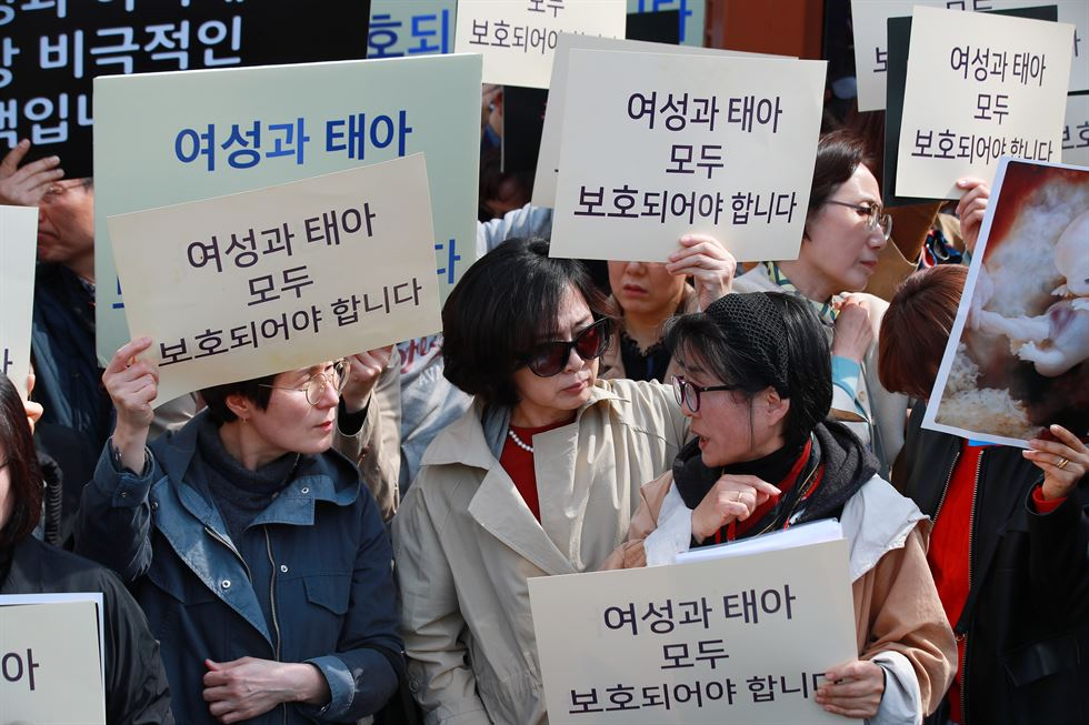 Abortion rights activists outside the Constitutional Court in central Seoul burst into tears after hearing the verdict ruling the abortion ban unconstitutional, Thursday. / Yonhap