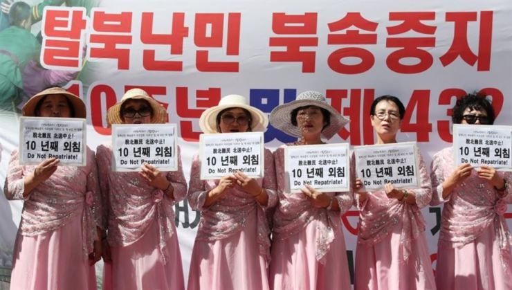 Participants in a street rally hold signs saying North Korean defectors should not be repatriated, in front of the Seoul Central Post Office in Seoul in this file photo taken Sept. 5, 2018. Yonhap