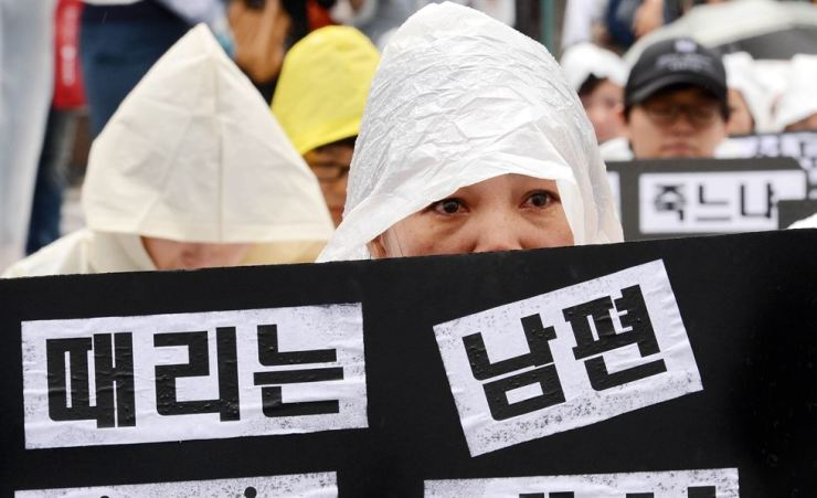 A participant sheds tears during a memorial event in front of Deoksu Palace in Seoul for marriage migrant women who were killed by their husbands, in this 2012 photo. / Korea Times file