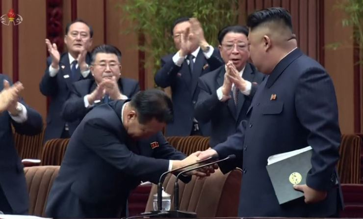 North Korean leader Kim Jong-un shakes hands with an official after being-re-elected as chairman of the North's state affairs commission. / Yonhap