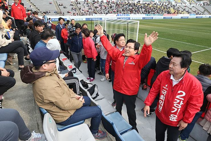 Liberty Korea Party (LKP) Chairman Hwang Kyo-ahn raises his hands in a move to support the election campaign of the party's by-election candidate Kang Ki-yoon, right, at Changwon Football Center, Saturday. Courtesy of LKP
