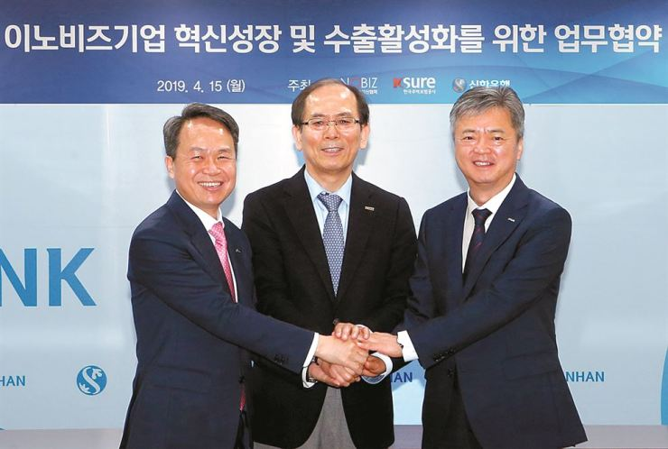 Shinhan Bank CEO Jin Ok-dong, left, INNOBIZ President Cho Hong-rae, center, and Korea Trade Insurance Corp. Chairman Lee In-ho put their hands together at the bank's headquarters in Seoul, April 15, after signing a memorandum of understanding (MOU) to set up a joint platform to help innovative companies. Courtesy of Shinhan Bank
