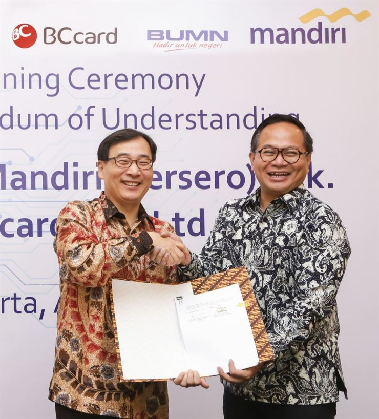 BC Card CEO Lee Mun-hwan, left, and Bank Mandiri CEO Kartika Wirjoatmodjo shake hands after agreeing to boost their digital partnership at the latter's headquarters in Jakarta, Indonesia, Monday. Courtesy of BC Card