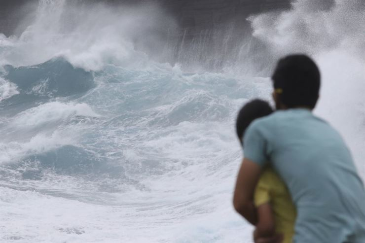 In this Aug. 24, 2018 file photo, a man and his son watch as waves crash off sea cliffs along the southeast shore of Oahu as Hurricane Lane approaches Honolulu. Some of Hawaii's most iconic beaches could soon be underwater as rising sea levels caused by global warming overtake its white sand beaches and bustling city streets. (AP Photo/Caleb Jones, File)