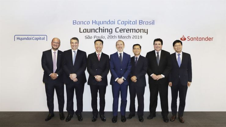 Hwang Yoo-no, third from left, global president of Hyundai Capital, and Banco Santander Brasil CFO Angel Santodomingo, fourth from left, pose with other officials at their joint venture launch event in Sao Paulo, Brazil, March 20. Courtesy of Hyundai Capital