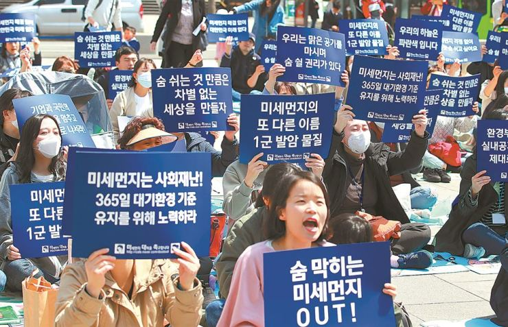 Members of an online community stage a rally at Gwanghwamun Square in central Seoul, Monday, urging the government to come up with measures against fine dust. / Yonhap
