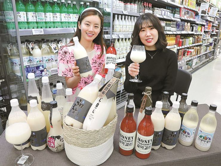 Models pose with premium makgeolli, traditional rice liquor, at an E-mart store in Seoul, Monday. According to E-mart, the sales of makgeolli jumped 24.6 percent in the first quarter of 2019 due to rising popularity among people in their 20s and 30s because of the diverse and premium flavors of the beverage. Yonhap