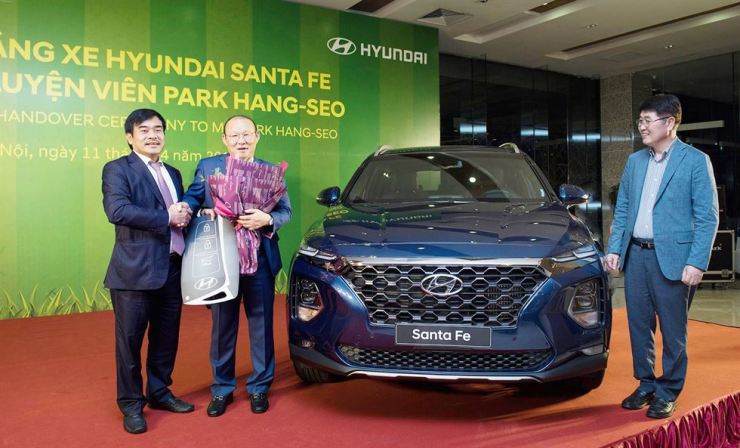 Korean head coach of the Vietnamese national football team Park Hang-seo, second from left, poses with Thanh Cong Group Chairman Nguyen Anh Tuan, left, during a ceremony receiving a Hyundai Santa Fe SUV at the latter's headquarters in Hanoi, Thursday. The vehicle was manufactured by Hyundai Thanh Cong Manufacturing Vietnam, a joint body of Thanh Cong Group and Hyundai Motor. Courtesy of Hyundai Motor