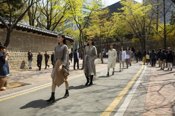 Models donning Bowlloon's spring collection walk down the street next to Deoksu Palace walls as part of Seoul 365 Fashion Show, Monday. / Courtesy of Seoul Metropolitan Government
