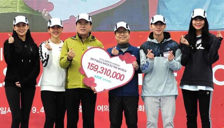 Korea Exchange CEO Jung Ji-won, third from right, poses with Child Fund Korea Chairman Lee Jae-hoon, third from left, during the 2019 Bulls Race to the World marathon event at Yeouido Park in Seoul, Saturday. The exchange donated 159.3 million won to help unfortunate children. / Courtesy of Korea Exchange