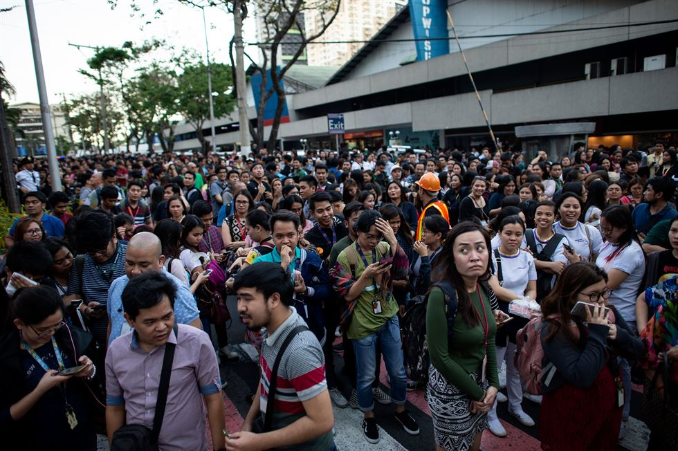 Wearing protective helmets, employees evacuate their office building following an earthquake in Manila, Philippines Monday, April 22, 2019. A strong earthquake has shaken the area around the Philippine capital, prompting thousands of people to flee to safety. AP