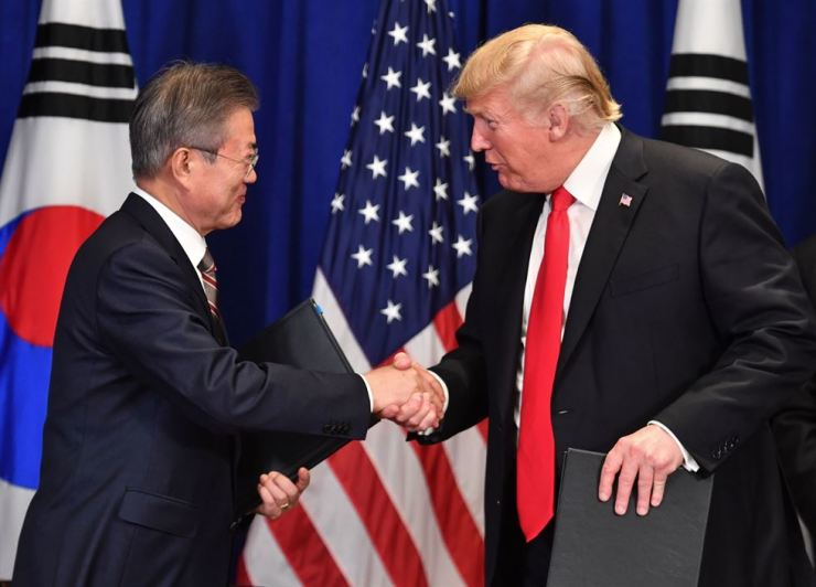 In this file photo taken on Sept. 24, 2018 U.S. President Donald Trump, right, and South Korean President Moon Jae-in shake hands after signing a trade agreement at a bilateral meeting in New York, a day before the start of the General Debate of the 73rd session of the General Assembly. AFP-Yonhap