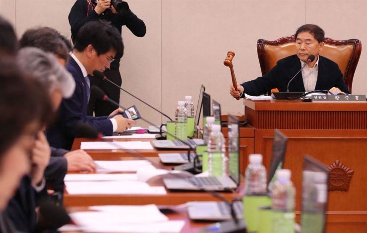 Rep. Hwang Ju-hong, chairman of the Agriculture, Food, Rural Affairs, Oceans and Fisheries Committee, holds the gavel after the committee adopted the hearing report on oceans minister nominee Moon Seong-hyeok at the National Assembly, Tuesday. / Yonhap