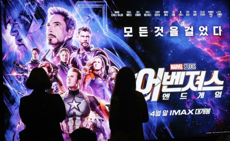 Moviegoers stand in front of a poster for the film 'Avengers: Endgame' at a local theater in Seoul, Thursday. / Yonhap